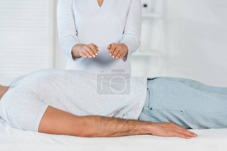 Photo for Female healer with hands above body of man - Royalty Free Image