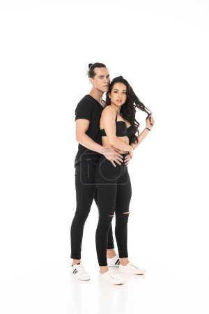 Photo for Full length view of couple in black clothes embracing isolated on white - Royalty Free Image