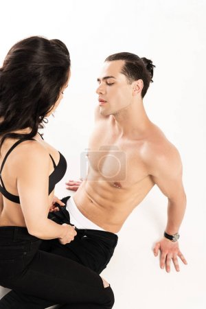 Foto de Cropped view of sexy girl undressing boyfriend isolated on white - Imagen libre de derechos