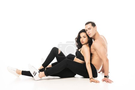 Photo for Sexy couple sitting on floor and looking at camera on white - Royalty Free Image