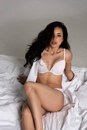 Photo pour Sexy jeune femme en sous-vêtements blancs assis sur le lit isolé sur gris - image libre de droit