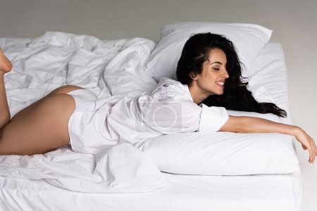 Photo for Smiling sexy girl in white shirt lying on bed - Royalty Free Image