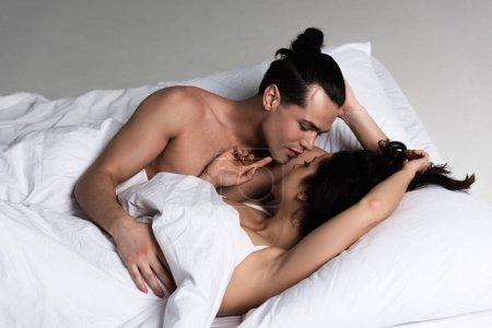 Photo pour Déshabillé sexy couple couché dans lit et regarder l 'autre - image libre de droit