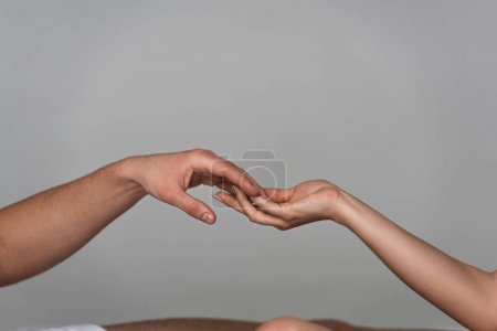 Photo for Partial view of young couple touching hands isolated on grey - Royalty Free Image