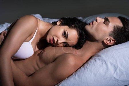 Photo pour Déshabillé sexy jeune couple couché sur le lit ensemble - image libre de droit