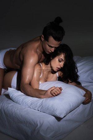 Photo pour Sexy couple déshabillé tenant la main tout en étant couché sur le lit - image libre de droit