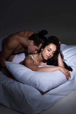 Photo pour Homme torse nu embrasser femme sexy tout en étant couché sur le lit dans l'obscurité - image libre de droit