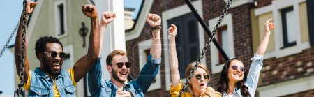 Photo for Panoramic shot of cheerful group of multicultural friends in sunglasses celebrating triumph - Royalty Free Image