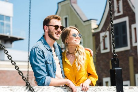 Foto de Cheerful woman and handsome man in sunglasses standing and smiling outside - Imagen libre de derechos