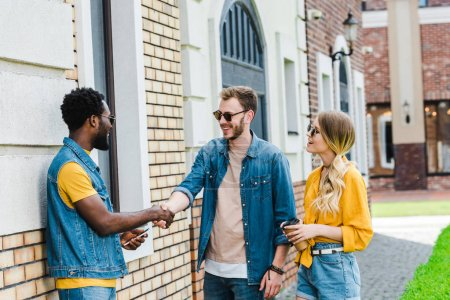 Photo pour Cheerful multicultural men shaking hands near happy woman with paper cup - image libre de droit