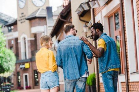 Photo pour Happy multicultural friends walking and smiling outside - image libre de droit