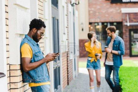 Photo pour Foyer sélectif du bel homme américain africain dans des lunettes de soleil utilisant le smartphone à l'extérieur - image libre de droit
