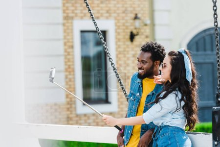 Photo pour Attractive woman showing peace sign near handsome african american man while  taking selfie and holding selfie stick - image libre de droit