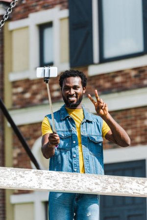 Photo pour Happy african american man showing peace sign while holding selfie stick and talking selfie - image libre de droit