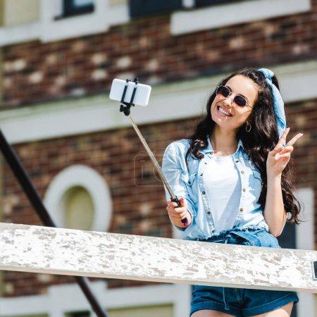 Photo pour Femme heureux retenant le bâton de selfie et prenant le selfie tout en affichant le signe de paix - image libre de droit