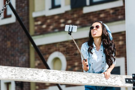 Photo for Young woman holding selfie stick and taking selfie while showing tongue - Royalty Free Image