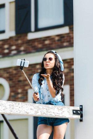 Photo pour Jeune femme retenant le bâton de selfie et prenant le selfie tout en envoyant le baiser d'air - image libre de droit
