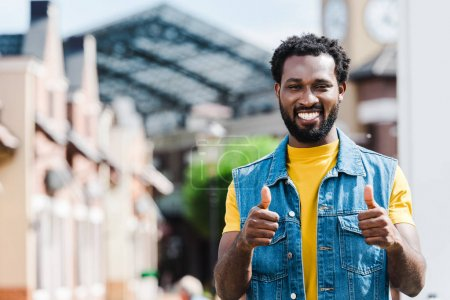 Photo for Cheerful african american man showing thumbs up while looking at camera - Royalty Free Image