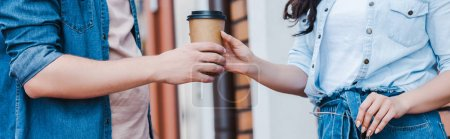 Photo for Panoramic shot of man giving paper cup to woman while standing outside - Royalty Free Image