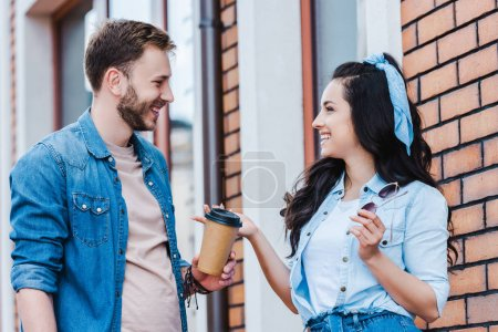 Photo for Happy man giving paper cup to attractive woman while standing outside - Royalty Free Image