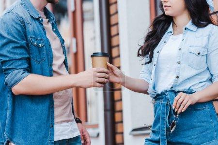 Photo pour Vue recadrée de l'homme donnant tasse en papier à la femme tout en se tenant à l'extérieur - image libre de droit