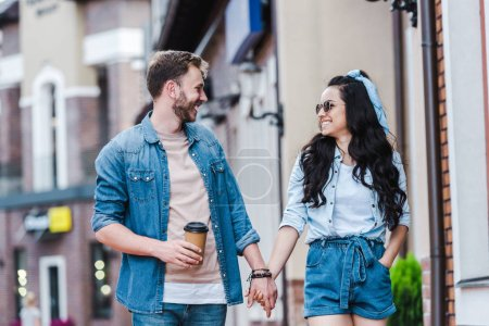 Photo for Cheerful woman with hand in pocket walking and holding hands with man - Royalty Free Image