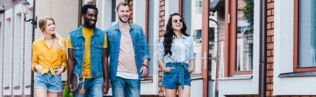 Photo for Panoramic shot of happy girls with hands in pockets walking with cheerful multicultural friends - Royalty Free Image