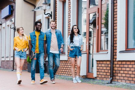 Photo for Happy girls with hands in pockets walking with cheerful multicultural friends - Royalty Free Image