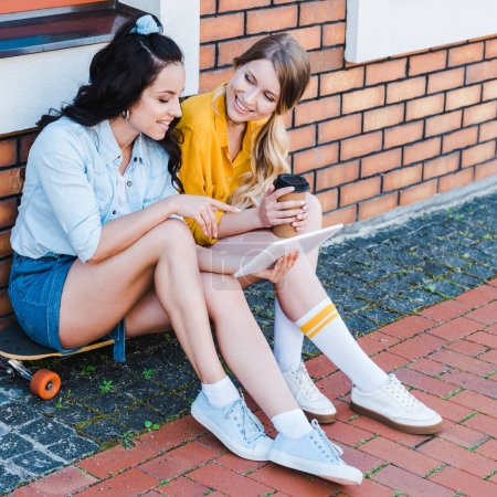 Photo for Happy woman pointing with finger at digital tablet while sitting on penny board with friend - Royalty Free Image