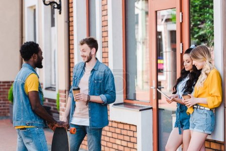 cheerful multicultural men talking while standing near happy girls using digital tablet