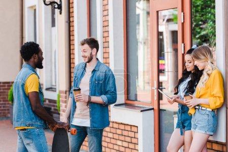 Foto de Hombres alegres multiculturales hablando mientras están de pie cerca de chicas felices usando tableta digital - Imagen libre de derechos