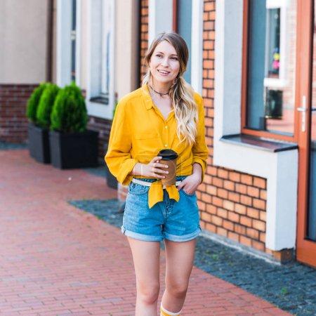 fröhliche Frau mit Pappbecher auf der Straße