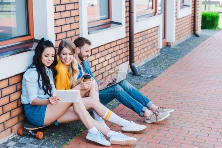 Photo for Happy women using digital tablet while sitting on penny board near man with laptop - Royalty Free Image