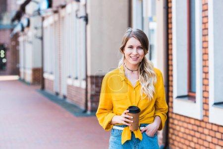 Glückliche Frau mit Pappbecher auf der Straße