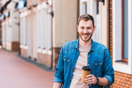 Photo for Cheerful handsome man holding paper cup and smiling near building - Royalty Free Image