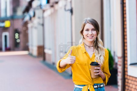Photo for Happy  woman holding paper cup while standing on street and showing thumb up - Royalty Free Image