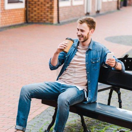 Photo pour Homme gai retenant la tasse et le smartphone de papier tout en s'asseyant sur le banc - image libre de droit
