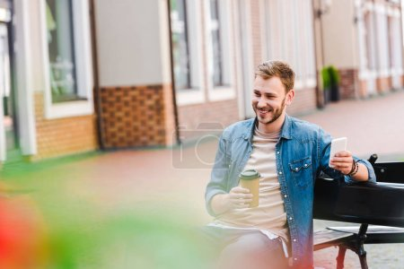 Photo for Selective focus of cheerful man holding paper cup and smartphone while sitting on bench - Royalty Free Image