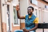 """Постер, картина, фотообои """"happy african american man waving hand while holding paper cup """""""