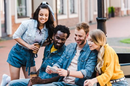 happy multicultural friends looking at smartphone while sitting on bench