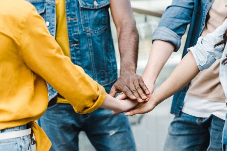 Photo for Cropped view of multicultural friends putting hands together - Royalty Free Image