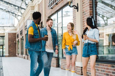 Photo for Cheerful multicultural group of friends with paper cups standing near building - Royalty Free Image