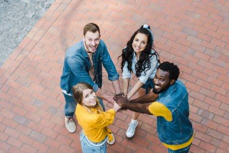 Photo pour Vue aérienne des amis multiculturels joyeux mettant des mains ensemble et regardant l'appareil-photo - image libre de droit