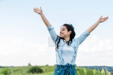 Photo for Cheerful young woman with  closed eyes and outstretched hands - Royalty Free Image