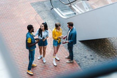 Photo for Overhead view of cheerful multicultural friends talking while standing with disposable cups - Royalty Free Image