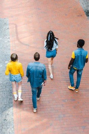 Photo pour Back view of multicultural friends walking together - image libre de droit