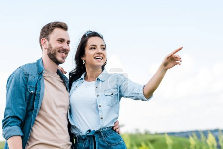 Photo for Cheerful and attractive girl smiling while pointing with finger near handsome man - Royalty Free Image