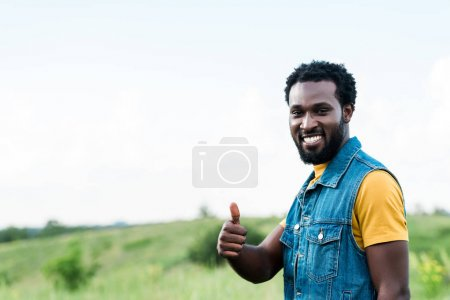 Photo for Cheerful african american man standing and showing thumb up - Royalty Free Image
