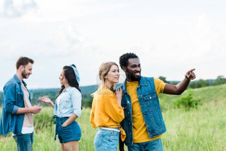 happy african american man pointing with finger while standing with girl near friends