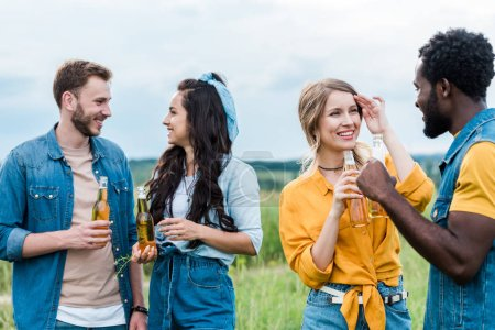 Photo for Cheerful multicultural men and women holding bottles with beer - Royalty Free Image